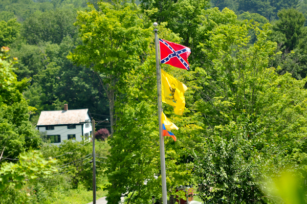 "The confederate battle flag flying at our neighbors home, above the Gadsen ""Don't Tread on Me"" flag and the flag of Columbia below it.  In the distance is our ancestral farmhouse, built circa 1810."